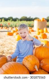 smiling little boy holding pumpkin at pumpkin patch