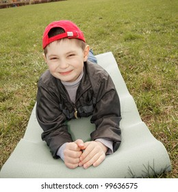 Smiling little boy laying down on mat outdoors