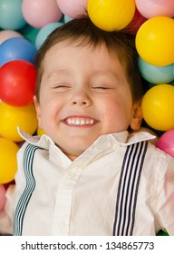 Smiling little boy lying in colorful balls
