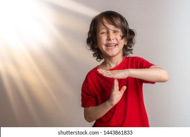 Smiling little  boy making a pause or break time hand gesture