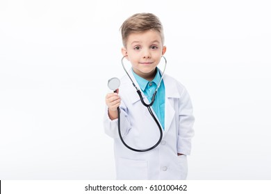Smiling little boy in medical uniform holding stethoscope and looking at camera isolated on white