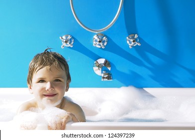 Smiling little boy peeking over the top of a frothy bubble bath against a blue wall