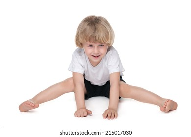 A smiling little boy performs gymnastic exercises on the white background