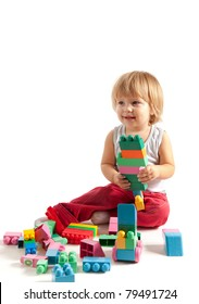 Smiling little boy playing with blocks, studio shot