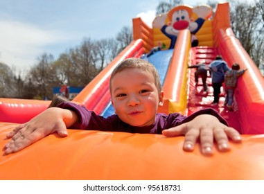 Smiling little boy playing on inflatable slide, looking at camera