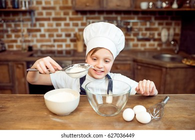 smiling little boy pouring flour in bowl