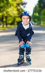 Smiling little boy rollerblading down the sidewalk
