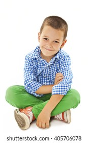 Smiling little boy sitting down on floor and looking at camera. Isolated on white background