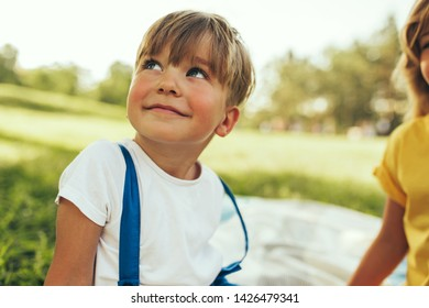 Smiling little boy sitting on the blanket at nature background. Happy child enjoying summertime with his sister in the park. Handsome kid smiling and having fun on sunlight outdoors. Childhood