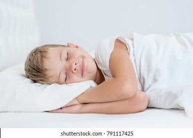 Smiling little boy sleeping on the bed