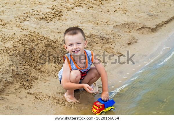 smiling-little-boy-squatting-toy-600w-18