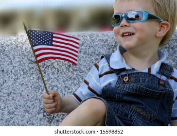 Smiling Little boy in sunglasses holding an American Flag, Fourth of July