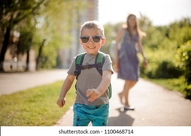 Smiling little boy in sunglasses walking down the street with his mother on sunny summer day