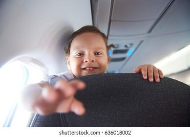 Smiling little boy travel  in airlane. Child air plane passenger
