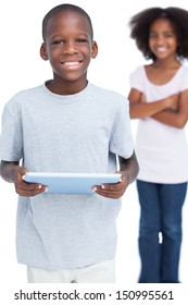 Smiling little boy using tablet pc with his sister behind him