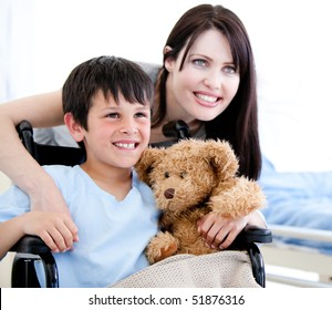 Smiling little boy in a wheelchair with his mother in a hospital