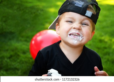 A smiling little boy with white frosting on his face