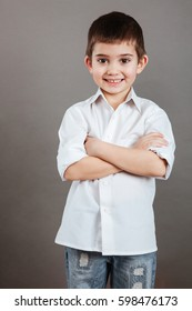 Smiling little boy in white shirt standing with arms crossed over grey background