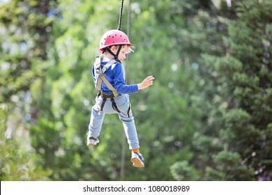 smiling little boy ziplining in treetop adventure park, healthy active lifestyle concept