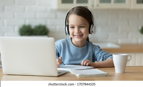Smiling little Caucasian girl in headphones handwrite study online using laptop at home, cute happy small child in earphones take Internet web lesson or class on computer, homeschooling concept