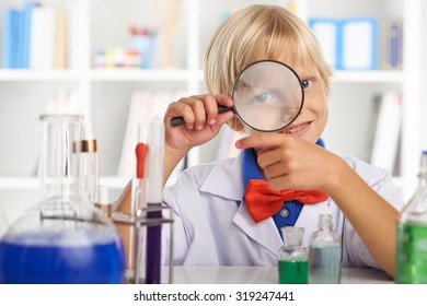 Smiling little chemist looking through magnifying glass and pointing at chemical glassware