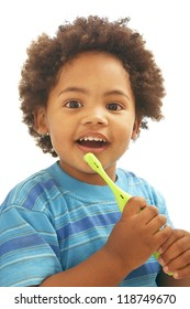 Smiling little child with afro hairstyle, holding green toothbrush on white background