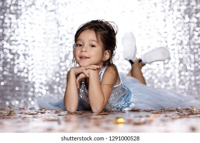 smiling little child girl in blue dress lying on the floor with confetti on background with silver bokeh. birtday party