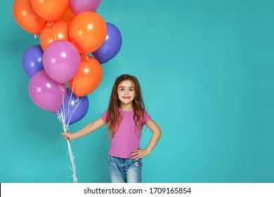 Smiling little child girl in pink t-shirt posing with bright colorful air balloons isolated on blue background. birthday party. space for text
