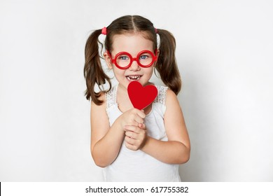 smiling little child in red toy glasses