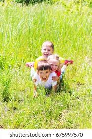Smiling little children lying on green grass. Happy boys and girl.