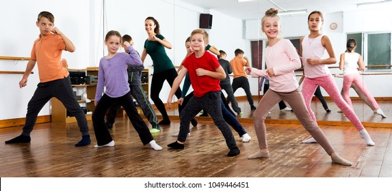 Smiling little children studying modern style dance in class