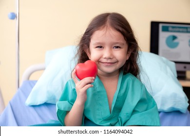 smiling little cute girl holding red heart shaped application and looking at camera. hope,health,love,happiness, people,donate and family insurance concept. happy child gesture holding heart in hands