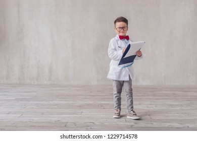 Smiling little doctor with clipboard in studio