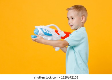 Smiling little fun male fair-haired brown-eyed kid boy 5-6 years old wearing stylish blue turquoise t-shirt polo hold in hand toy water gun isolated on yellow color background, child studio portrait