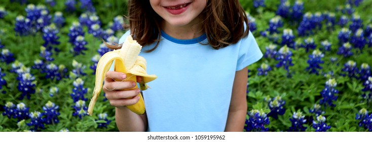 Smiling little girl with banana on bluebonnets field background