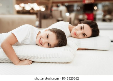 Smiling little girl with beautiful mother hugs pillows in store of orthopedic mattresses. Testing softness of pillow. Check softness of orthopedic pillow.