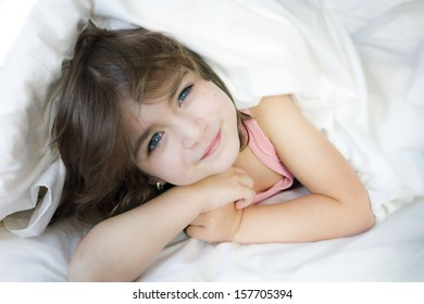 Smiling little girl in the bed under cover
