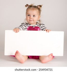 Smiling little girl behind empty white board