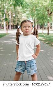 smiling little girl in blank white t-shirt standing in park