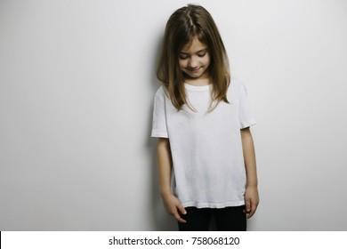 Smiling little girl in blank white t-shirt, design concept, mock-up of blank white t-shirt
