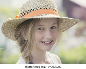 smiling little girl with blonde hair and hat