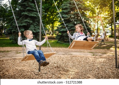 Smiling little girl and boy on a swing. Children playing outdoors in summer.