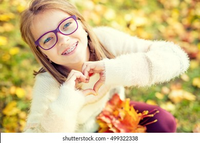 Smiling little girl with braces and glasses showing heart with hands.