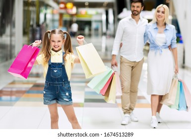 Smiling Little Girl Carrying Shopper Bags Buying Clothes With Parents In Shopping Mall On Weekend. Selective Focus