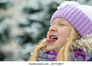 smiling little girl catching a snowflakes with her tongue