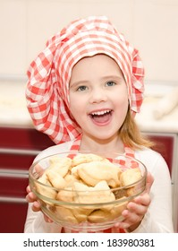 Smiling little girl in chef hat holding bowl with cookies in the kitchen