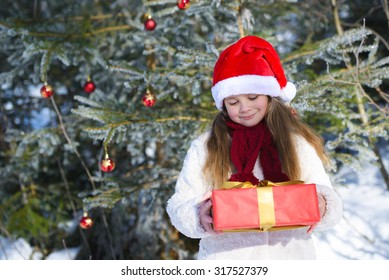 Smiling  little girl with christmas gift in the winter forest