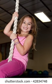 Smiling little girl climbing on rope