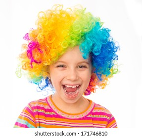 smiling little girl in clown wig isolated on white background