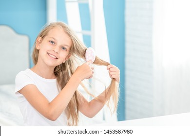 Smiling little girl combing hair in the morning at home. Empty space for text